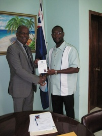 L to R: Minister Hon. Dennis Richardson receiving his belonger certificate from Anguilla Minister Hon. Jerome Roberts.