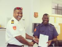 L to R: Local Commander of the Fire Brigade section Saba, Julio Every, presented James Hassell with his Decree and his stripes. (Photo contributed)