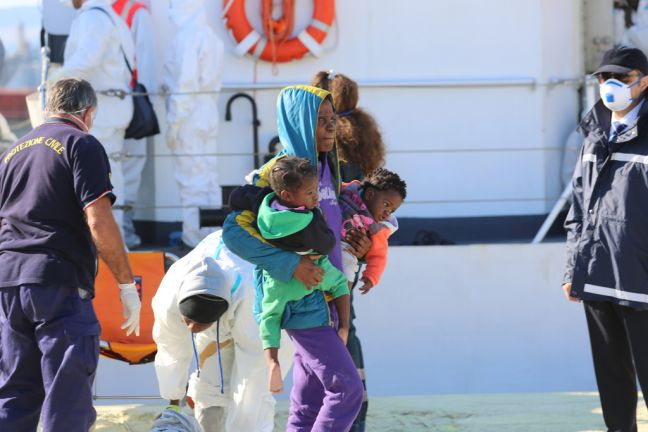 A woman carries her two babies as she disembarks the boat that rescued her while attempting to cross the Mediterranean Sea from Libya to Italy. (file) UNHCR/Francesco Malavolta