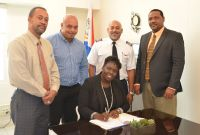 Minister Mellissa Arrindell-Doncher (sitting center) signs the economic permit for SXM Airways surrounded by (from left): Head of Civil Aviation Lou Halley and Directors of SXM Airways Michel Carter, Jeff Oliver and Elvis Queeley.