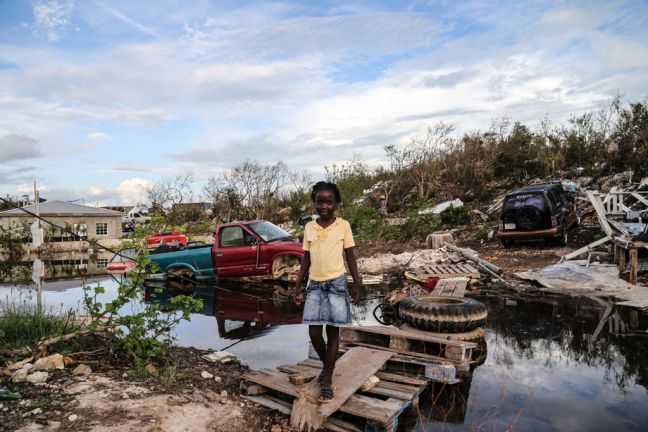 A seven-year-old girl crosses an improvised wooden bridge which she built after Hurricane Irma caused severe damaged in the Five Cays' settlement of Providenciales, in the Turks and Caicos Islands. Photo: UNICEF/Moreno Gonzalez