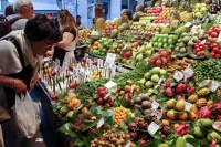 A shopper sorts through fruit at a market in Barcelona, Spain. Photo: FAO/Alessia Pierdomenico