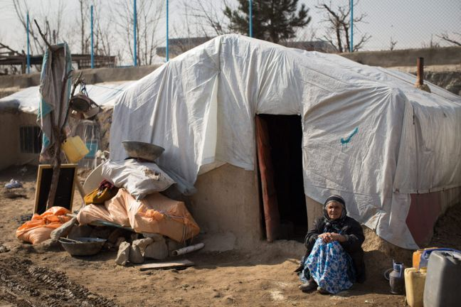 An elderly woman sits outside her makeshift dwelling in Afghanistan. Photo: WFP/Eoin Casey