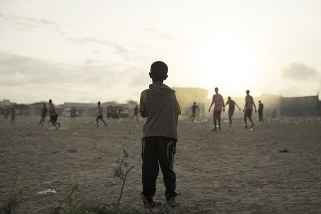 A young child looks on as older boys play football next to a camp for internally displaced persons (IDP) in Mogadishu, Somalia. UN Photo/Tobin Jones