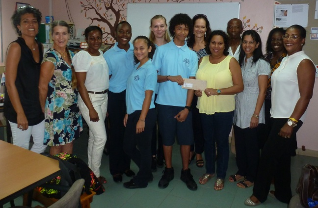 Island Gems President Alita Singh symbolically presents the air ticket to Reno Brooks of the MPC Mathematics A-Lympiad team. Also in photo are other Island Gems' team members and MPC representatives.