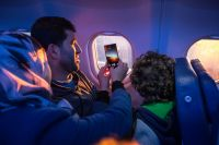 Passengers gaze out the window of their plane and take pictures as they fly over the Swiss Alps. Photo: IOM/Muse Mohammed