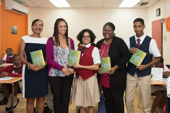 "UTS Marketing and Communication Officer Ivy Lambert (second left) handing over a copy of the HYPE Agenda 2017-2018 to CBA student Xocxhiquetzal ""Xochi"" Gonzalez (third left), who designed the cover of the Agenda, while CBA Director Claudette Forsythe-Labega (left), CBA Visual Arts Teacher Zetsia Shigemoto (fourth left) and a CBA student look on."