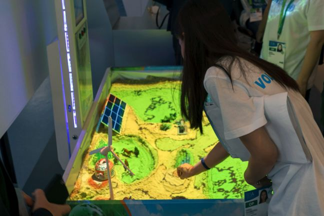A visitor explores the working of a solar and wind energy model at the UN pavilion at EXPO 2017. Photo: UNIDO