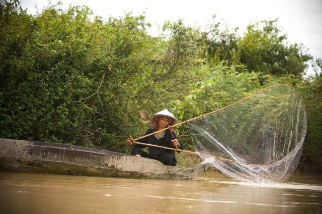 A woman casting a fishing net from a boat on the Tonle Sap River, Cambodia. Photo: FAO/A.K. Kimoto