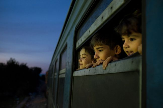 In the former Yugoslav Republic of Macedonia, three children look out of the window of a train, which was boarded by refugees primarily from Syria, Afghanistan and Iraq, at a reception centre for refugees and migrants, in Gevgelija. Photo: UNICEF/Ashley Gilbertson VII