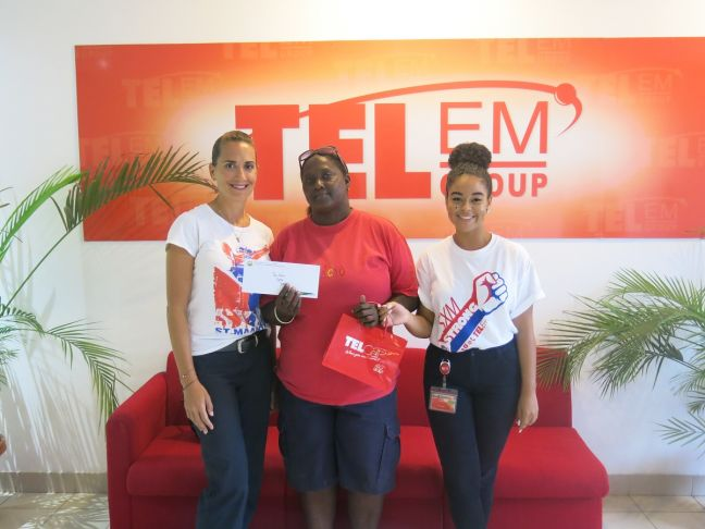 Lucky winner of the TelEm Group/TelCell St. Maarten Day SXM Campaign, Mrs. Dalidia Williams (Center) is picture with Rainforest Adventure representative Ms. Julie Zambrini (left) and TelEm Group representative Candice Teunis.