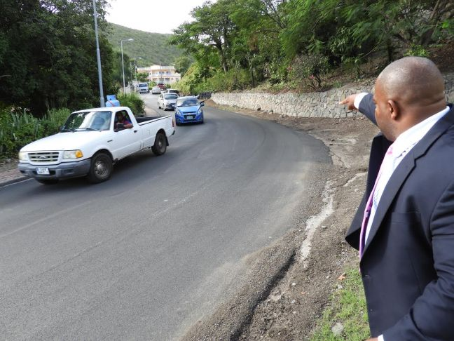 Honorable Minister C. Emmanuel pointing at the road in Mount William Hill.