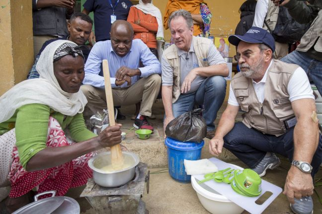In Ethiopia, IFAD's Gilbert Houngbo, WFP's David Beasley and FAO's José Graziano da Silva watch as a woman makes a nutritious porridge at a health centre in Tigray region. Photo: FAO/IFAD/WFP/Petterik Wiggers.