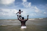 A four-year-old boy and his father Marshall Mejia, play in the water during a visit to the seashore, in their hometown of Dangriga, on the south-eastern coast of Belize. Photo: UNICEF/UN035756/LeMoyne