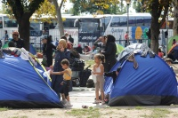 Children, women and men who have fled their homes amid the ongoing refugee and migrant crisis, stand outside small tents in a park next to the bus and train stations in Belgrade, the Serbian capital. Photo: UNICEF/ Shubuckl