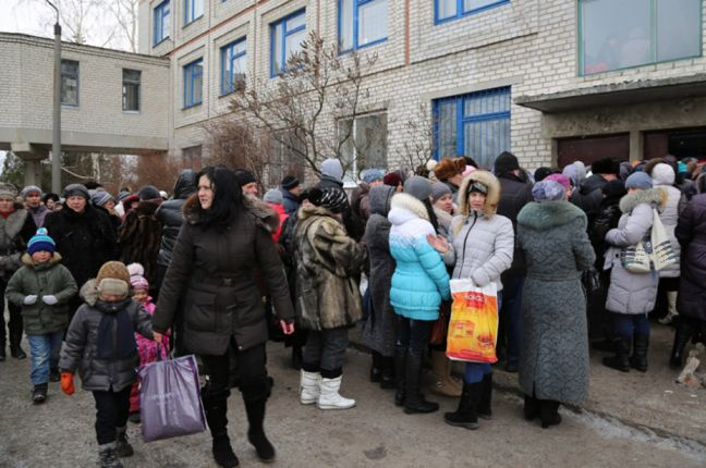 Displaced families and the elderly in Ukraine line up for WFP food vouchers, which enable them to obtain food including milk, fresh fruit, vegetables, eggs and meat. Photo: WFP/Abeer Etefa
