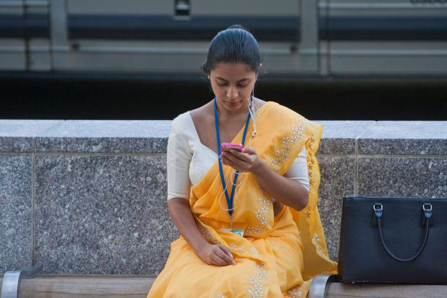 A young woman checking her smartphone, Washington DC. , USA. Photo: World Bank/Simone D. McCourtie