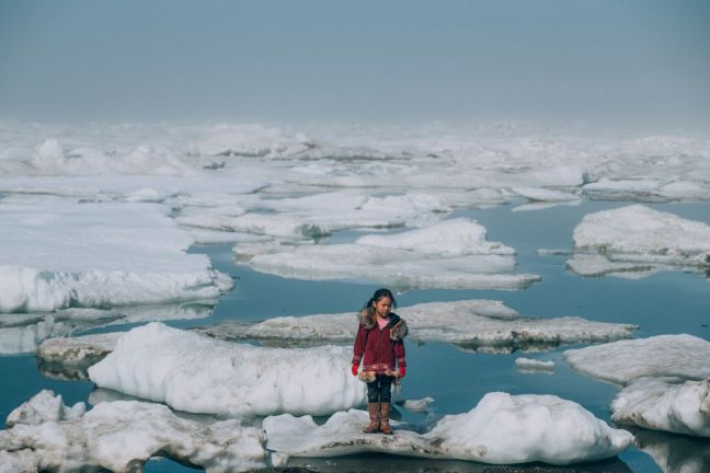 A girl from the Iñupiat community stands on a ice floe on a shore of the Arctic Ocean in Barrow, Alaska in the United States. The anomalous melting of the Arctic ice is one of the many effects of global warming that has a serious impact on the life of humans and the wildlife. Photo: UNICEF/Vlad Sokhin
