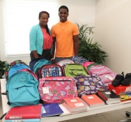 Minister Jacobs hands over Back to School Drive materials to Ki-Mani Olivacce