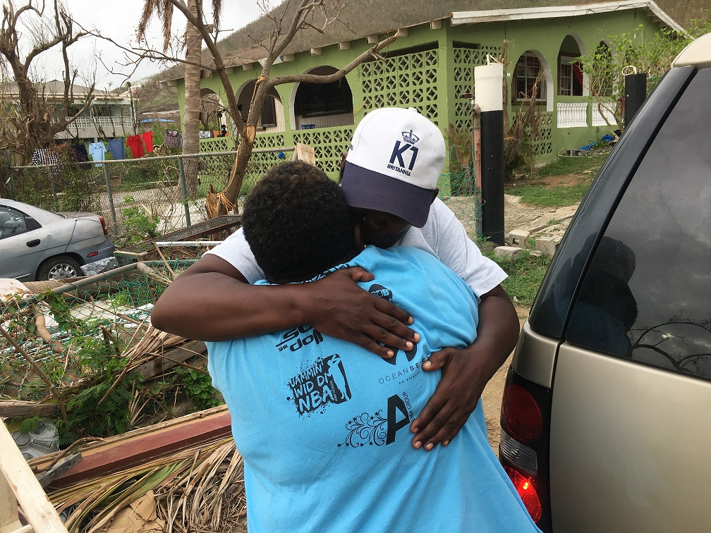 K1 volunteer embraces a local woman affected by the Hurricanes
