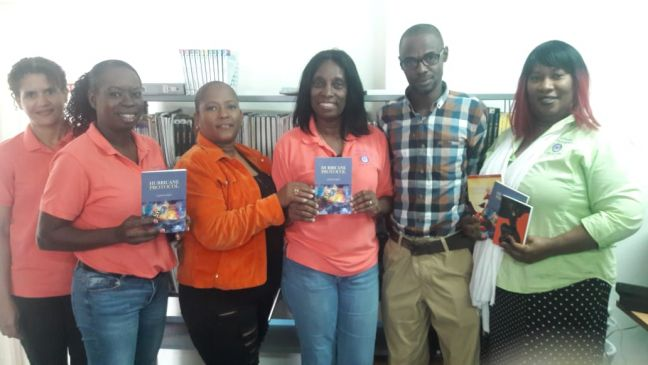 In the photo: Library director Hughes (3rd R) and librarians with books presented by HNP representatives Sorelis Peters-Mejia (3rd L; book launch committee) and W. Wilson (2nd R; volunteer). HNP photo.