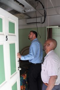 Minister of Tourism Stuart Johnson (left) looks at the damage to room #5 during a tour of LAMA Guest House on E.C. Richardson #19, while the hotel operator gives an explanation on the extent of the damage to the property caused by hurricane Irma in 2017.