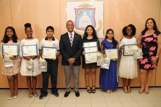 Minister Wycliffe Smith (centre) with Mrs. Yvette Halley (right) and student award recipients.