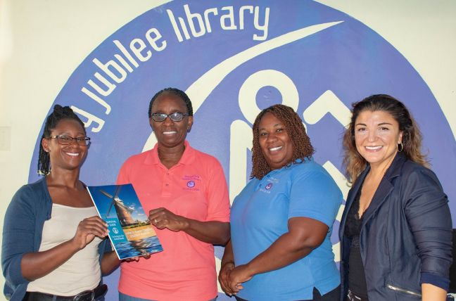 "(L-R): Library Interim Director, Irmin Hughes, Public Relations Officer Mariland Powell, Chapter Director, Carmencita P, and Zeynep Sabahoglu. Lamar receiving the sole copy of ""Unified St. Maarten Connection Student Manual: Survival Guide to living in the Netherlands"""