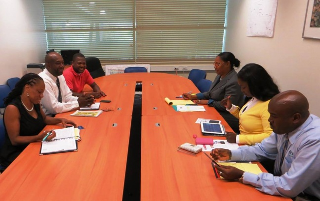 Representatives of the SXM Airport Marketing & Customer Service Department, table right (R-L): Jerome Gumbs, Audrey Jack, and Daphne Nicholson, meeting with St. Martin Book Fair Committee members, table left (L-R), Dr. Rhoda Arrindell, Shujah Reiph, Conneir Thelwell.