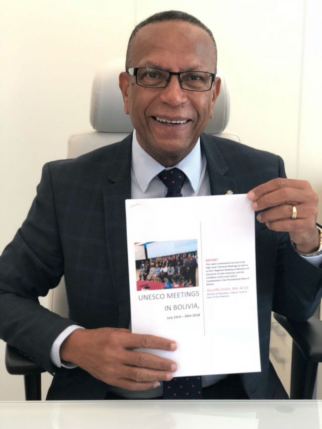 Minister Wycliffe Smith with a copy of his report on the Cochabamba Conference in hand.