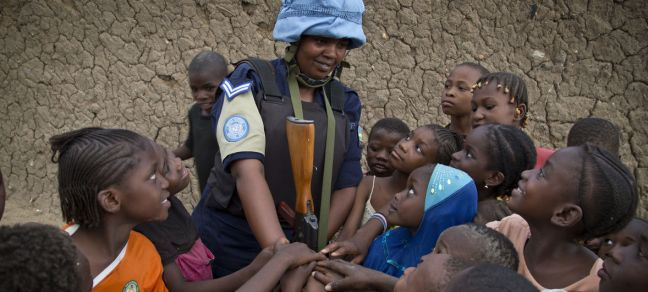 UN Photo/Marco Dormino A Rwandan peacekeeper from the UN Multidimensional Integrated Stabilization Mission in Mali (MINUSMA) Formed Police Unit (FPU) speaks with children while patrolling the streets of Gao in northern Mali.