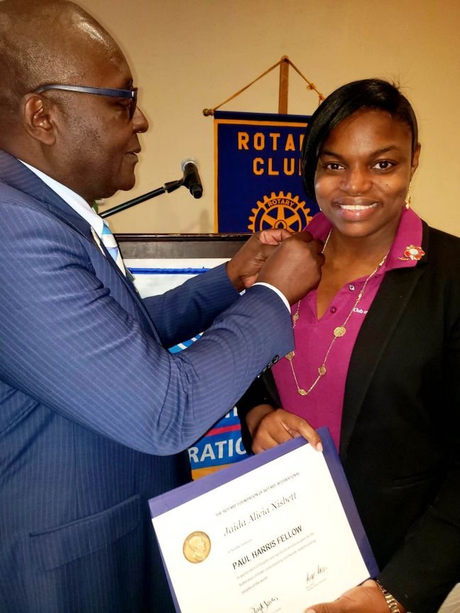 President Jaida Nisbett being pinned by District Governor Patrick Adizua with a Paul Harris Fellow lapel at the Rotary District 7020 Conference in Kingston, Jamaica.