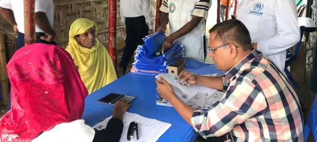 © UNHCR/Caroline Gluck A UNHCR officer helps register Rohingya refugees in Kutupalong Refugee Camp in Cox's Bazar, Bangladesh. (24 July 2019)