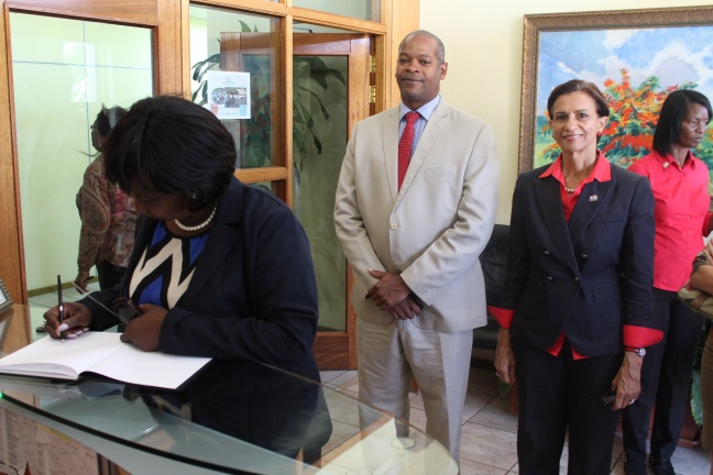 Minister Hon. Patricia Lourens-Philip signing the condolence register while Minister of Public Health Hon. Cornelius de Weever and Prime Minister Hon. Sarah Wescot-Williams look on.  DCOMM Photo