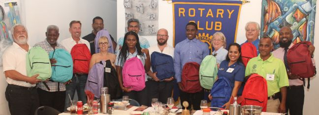 Mid Isle Rotarians with guests and Ki-Mani Olivacce displaying the backpacks.