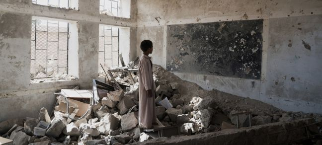 UNICEF/Clarke for UNOCHA A student stands in the ruins of one of his former classrooms, which was destroyed in June 2015, at the Aal Okab school in Saada, Yemen. Students now attend lessons in UNICEF tents nearby.