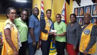 St. Maarten Lions Club President Carmen Lake hands over the donation check to Accessible Ventures with the student's family and other Lions members looking on.