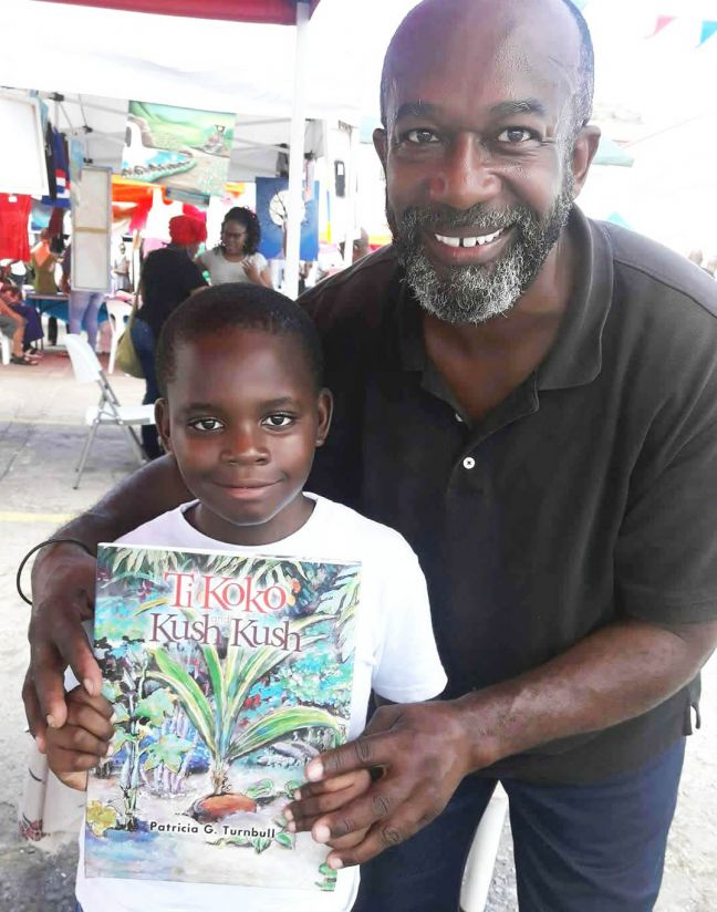 "Shujah and Timothy met again at SOS radio's Lazy Bay fair of ""Made in St. Martin/St. Maarten"" foods, books, and arts and crafts (3.31.18). As a thank you gift to Timothy and Joshua, Shujah presented Timothy with the newest published-in-St. Martin storybook, Ti Koko and Kush Kush by Virgin Islands author Dr. Patricia G. Turnbull. And the date of this year's St. Martin Book Fair? The island-wide ""book fair for the entire family"" will take place on June 1 – 2, 2018. (CLF photo.)"