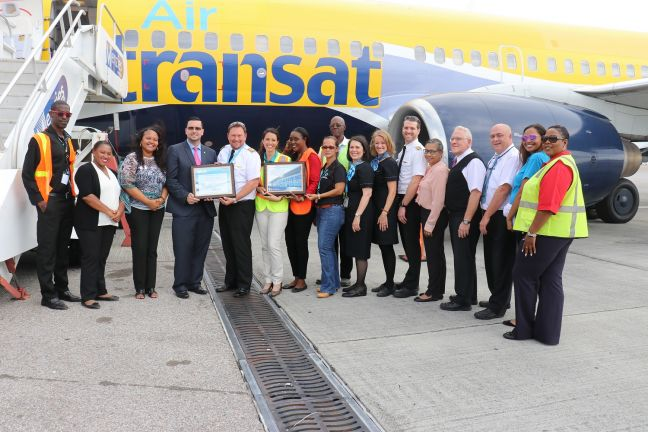 In the photo Minister Johnson (fourth from the left) hands a welcome plaque to Captain K.C. Aatecma to mark the return of Air Transat to St. Maarten.