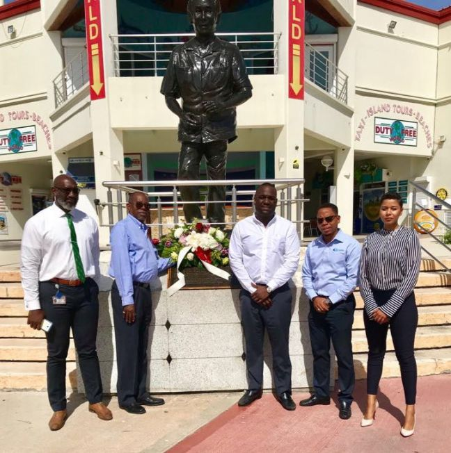 Members of the Management Team along with staff before laying a wreath at the statue of the late Dr. Claude Wathey.