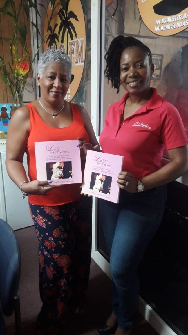 SOS Radio personalities Jacky Bute (l) and  Shirma France (r) posing with their books, Love is Forever...