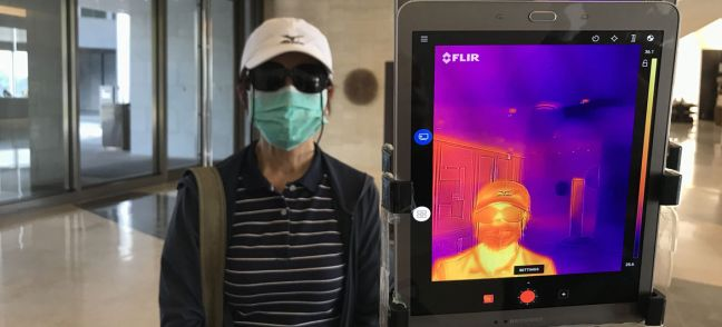 UN News/Jing Zhang An infrared thermometer is used to check the temperature of guests at a hotel entrance in Yangon, Myanmar.