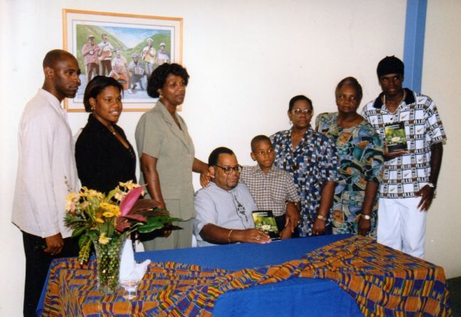 Louis L. Duzanson (center, seated) with family and guests holding copies of An Introduction to Government – Island territory of St. Maarten, at the book party, PJL, 2000. (© HNP photo.)