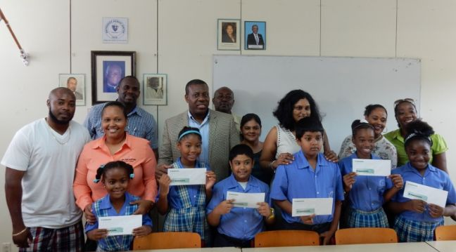 The 2016 NAGICO Little Stars pose with their scholarship vouchers and is flocked by their parents and teacher at the MAC school. (Photo contributed)