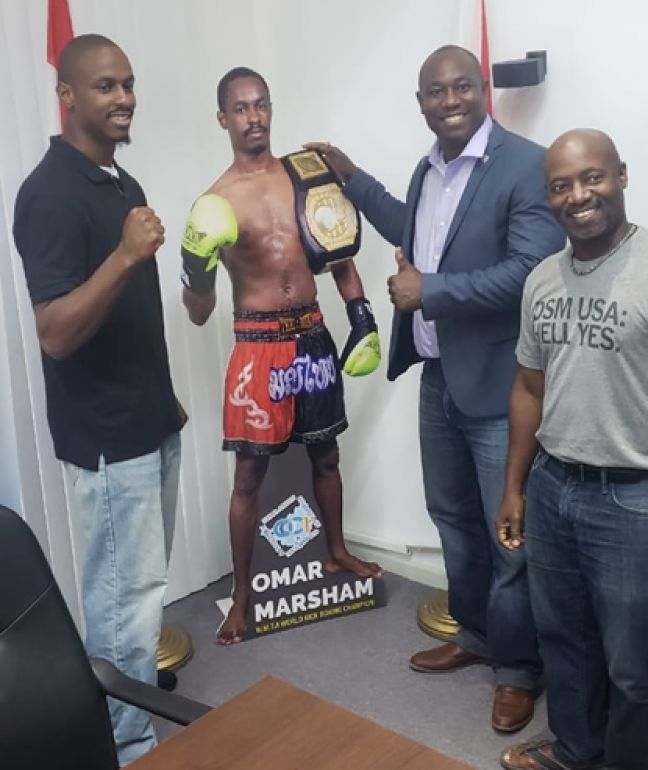 COCI Offices, Philipsburg, with cut-out of St. Maarten's very own Light Heavyweight Kickboxing Champion of the World, Omarie Marsham (left) with COCI President of the Board Benjamin Ortega (2nd from right) and COCI Executive Director Anastacio Baker (1st from right) looking on.