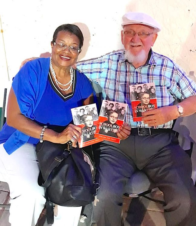 "Author Gerard van Veen (R) and educator Mrs. Bernadine van Veen, with copies of Schoolboy in Wartime during ""block party"" in Philipsburg. (credit G. van Veen)"