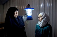 Syrian refugee Umfadi holds a solar powered lamp beside her 13-year-old niece Rama in her shelter at the Azraq refugee camp in Jordan. Photo: UNHCR/S. Baldwin