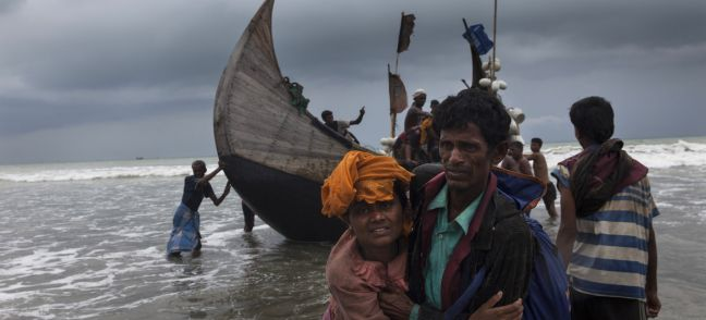 UNICEF/Patrick Brown A man helps a woman to the shore, as a boat arrives with Rohingya refugees in Teknaf, Cox's Bazar, Bangladesh. (file photo)