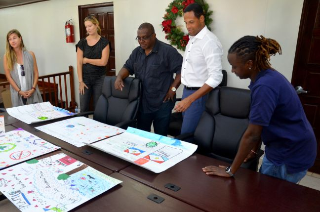 The petite committee, consisting of Commissioner Rolando Wilson (center), Island Secretary Tim Muller (second from right) and Protocol/GIS Head Saskia Matthew reviewing the posters. At left, Heli Böhm of Saba Nature Education and second from left, policy advisor Sarah van der Horn.