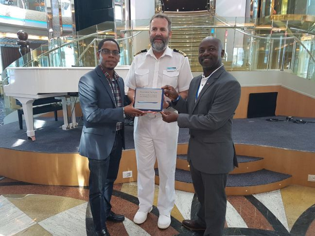 L to R: Port St. Maarten representative Alex Gumbs, Captain of Marella Discovery and Executive Director of the St. Maarten Chamber of Commerce & Industry Anastacio Baker, during an impromptu plaque exchange on Tuesday.